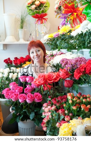 Middle-aged woman in her small  flower shop - stock photo