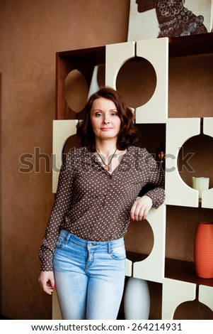 Middle-aged woman in jeans and a blouse standing near shelves - stock photo