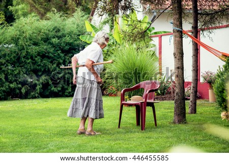 Middle-aged woman in the yard, intends to sit on a chair. - stock photo