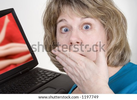 Middle-aged woman looks aghast at what is showing on her computer. Photo composite. - stock photo
