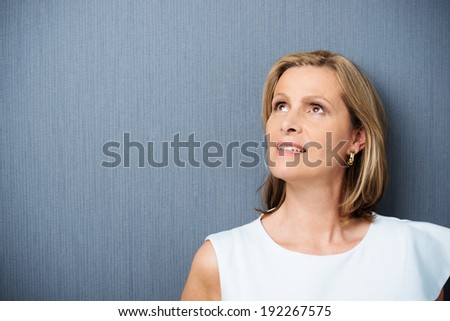 Middle-aged woman lost in thought staring up into the air with a contemplative expression against a dark grey background with copyspace - stock photo
