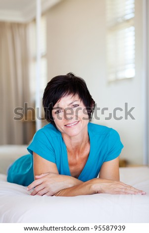 middle aged woman lying on bed relaxing - stock photo