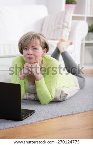 Middle aged woman lying on the floor with laptop