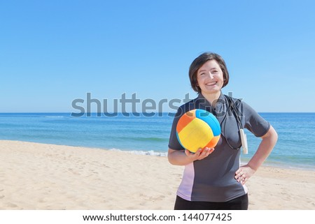 Middle-aged woman on the beach with a volleyball ball. Close-up. - stock photo