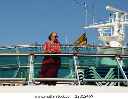 Middle-aged woman on the top deck of a cruise ship - stock photo