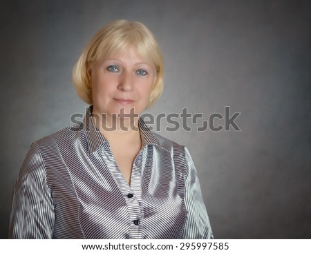 Middle aged woman portrait on dark background.