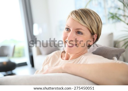 Middle-aged woman relaxing in sofa at home - stock photo