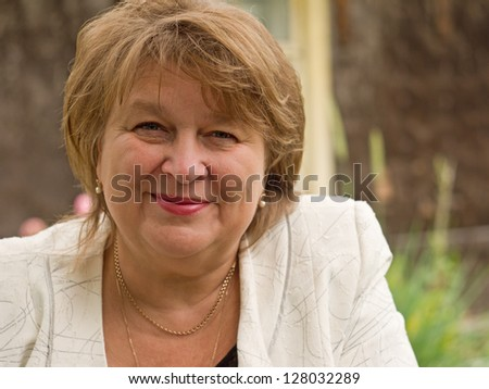 Middle-aged woman relaxing on a bench in sunny day - stock photo