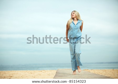 Middle aged woman resting at beach near the sea - stock photo