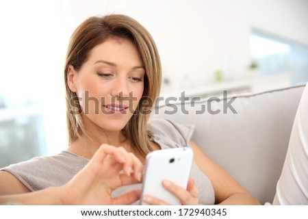 Middle-aged woman sending message with smartphone - stock photo