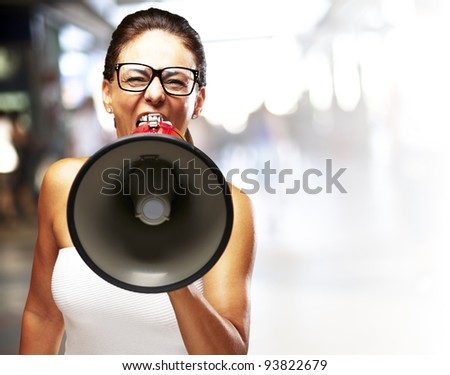 middle aged woman shouting with a megaphone at a busy place - stock photo