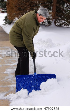 middle aged woman shoveling snow off sidewalk - stock photo