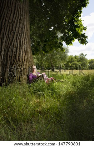Middle aged woman sitting beneath a tree with book - stock photo