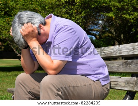 Middle-aged woman sitting on bench, head in hand in despair - stock photo