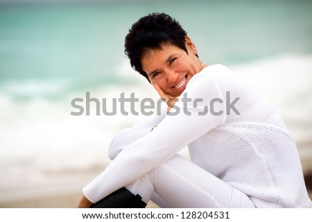 Middle aged woman sitting on the beach during the day, dress casual. Lifestyle image with a n healthy feeling.