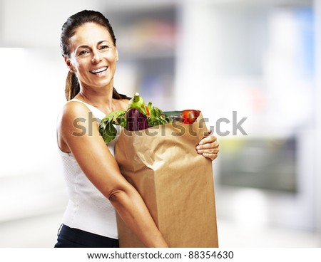 middle aged woman smiling and holding the purchase indoor - stock photo