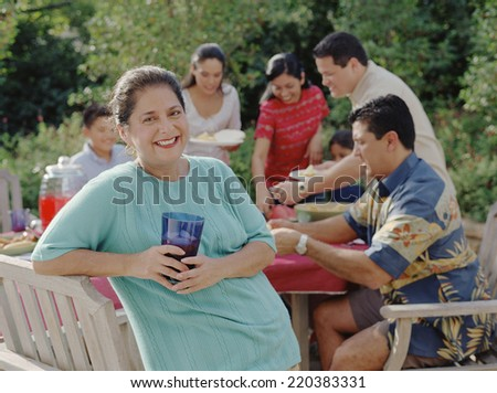Middle-aged woman smiling for the camera at a barbecue - stock photo