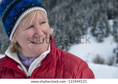 Middle aged woman smiling in winter snow