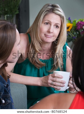 Middle-aged woman smirks while talking with friends - stock photo