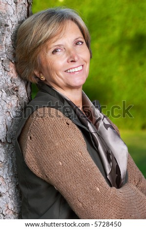 Middle aged woman standing by the tree. - stock photo