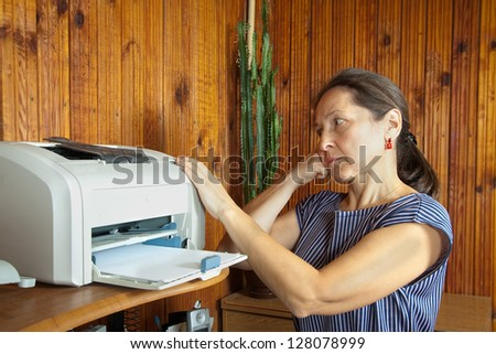 middle-aged woman standing near printer   in confused - stock photo