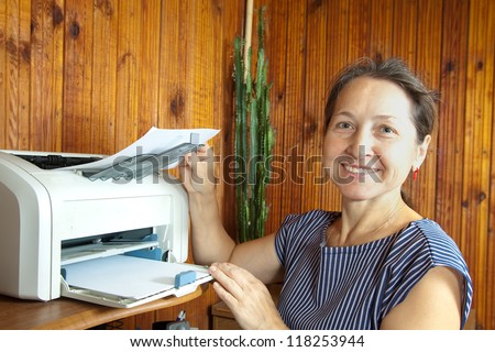 middle-aged woman standing near printer with paper