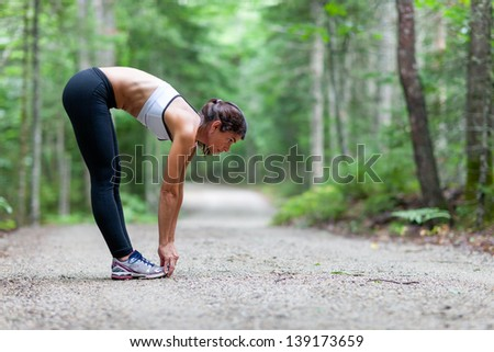 Middle aged woman stretching in the woods on a dirt road before a run - stock photo