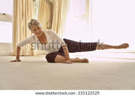Middle-Aged Woman Stretching on Floor - stock photo