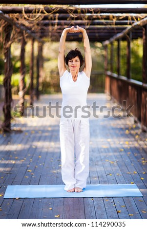middle aged woman stretching outdoors - stock photo