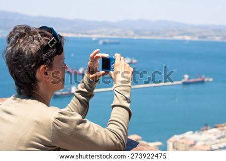 Middle aged woman taking photos using compact camera. - stock photo