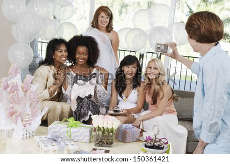 Middle aged woman taking pictures of friends at bridal shower - stock photo