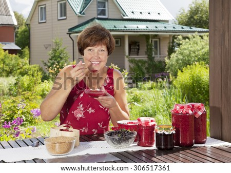 Middle aged woman tastes just her cooked raspberry jam  - stock photo