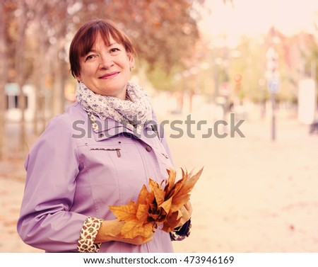 Middle-aged woman walking in autumn   park