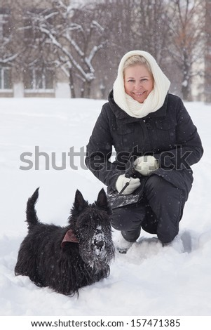 Middle aged woman walking with scottish terrier dog in winter. - stock photo