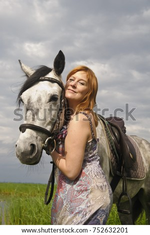 Middle-aged woman with a horse by the lake