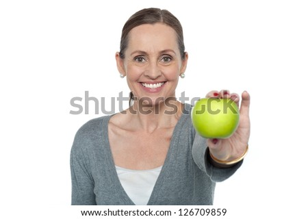 Middle aged woman with an apple in her outstretched arm, white background.