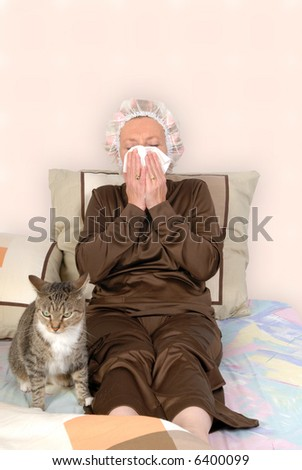 Middle aged woman with cold, sick in bed, blowing her nose.  Curlers and net in hair. Cat keeping her company - stock photo