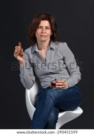 middle aged woman with glass of whiskey and cigar on black background  - stock photo