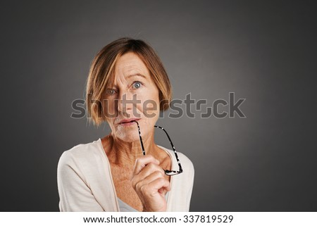 Middle-aged woman with glasses looking at camera, isolated on grey - stock photo