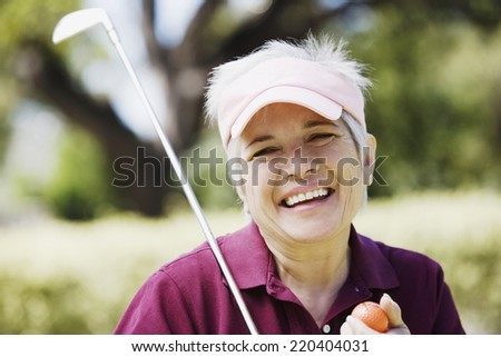 Middle-aged woman with golf club and golf ball - stock photo