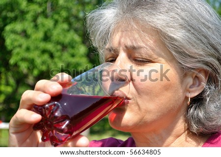 Middle-aged woman with pleasure drinking cherry juice
