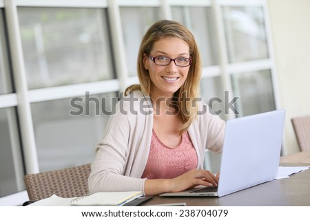Middle-aged woman working from home on laptop - stock photo