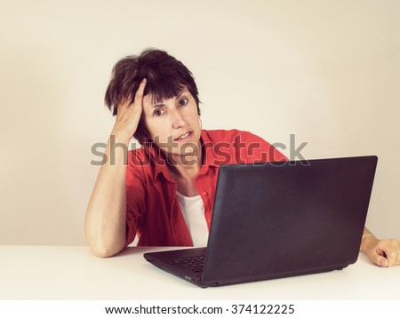 Middle aged woman working on laptop. Retro filtered image. - stock photo