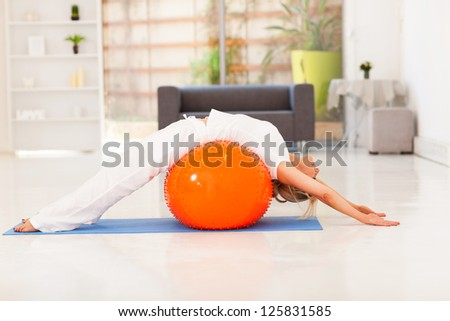 middle aged woman workout on exercise ball at home - stock photo