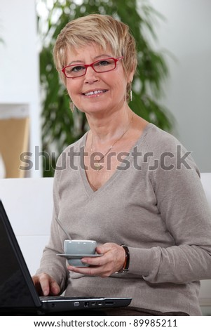 Middle-aged women drinking coffee whilst surfing the internet - stock photo
