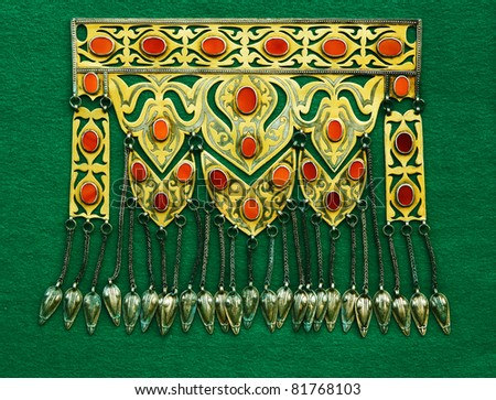 Middle-Asian traditional vintage accessory. Silver, gilding, semi-precious stones, east ornament. Isolated on dark green woollen cloth.