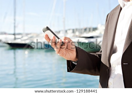 Middle body section of a businessman hand using a smart phone while standing on a luxury yachts marine during a sunny day. - stock photo
