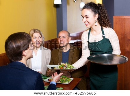 Middle class people enjoying food,happy waitress taking order. Focus on the waitress - stock photo