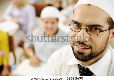 Middle East teacher in school classroom with children in background