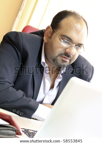 Middle eastern businessman working on laptop - stock photo